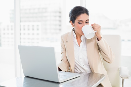 Cheerful businesswoman drinking from mug while working on laptop at the office photo