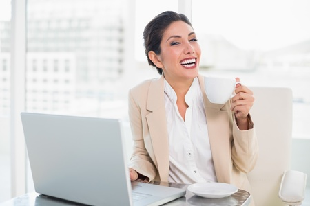 Laughing businesswoman holding cup while working on laptop in her office photo