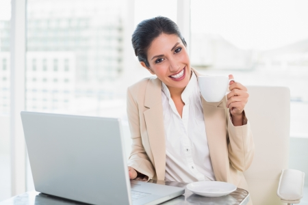 Happy businesswoman holding cup while working on laptop in her office photo