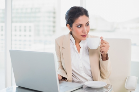 Thinking businesswoman holding cup while working on laptop in her office photo