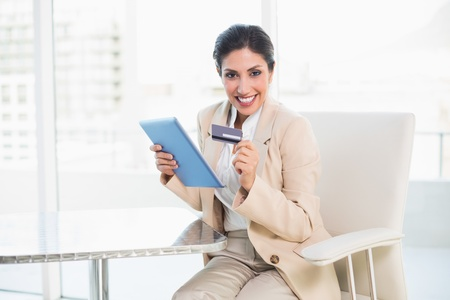 Excited businesswoman shopping online with tablet pc in her office photo