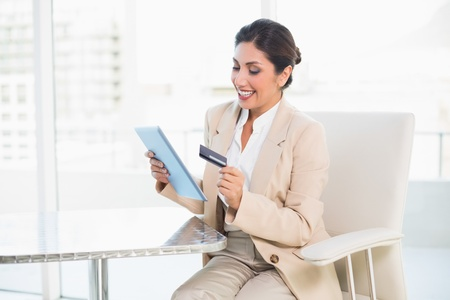 Cheerful businesswoman shopping online with tablet pc in her office photo