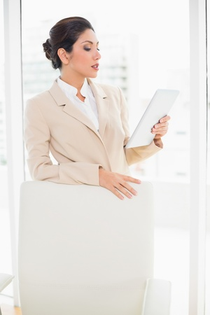 Businesswoman standing behind her chair holding tablet pc in her office photo