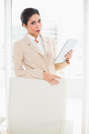 Frowning businesswoman standing behind her chair holding tablet pc in her office photo