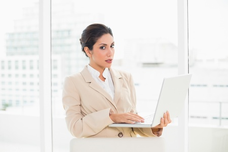 Frowning businesswoman standing behind her chair holding laptop in her office photo