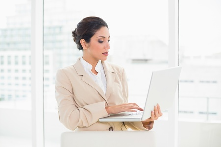 Serious businesswoman standing behind her chair holding laptop in her office photo