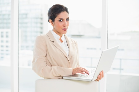 Smiling businesswoman standing behind her chair holding laptop in her office photo