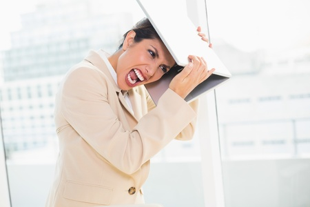 Crazed businesswoman hitting head off laptop in her office photo