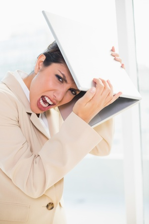 crazed: Crazed businesswoman hitting head off laptop looking at camera in her office Stock Photo