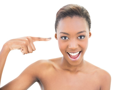 nude black women: Natural smiling beauty pointing at her temple on white background