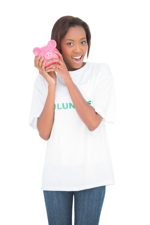 Smiling woman shaking piggy bank by her ear on white background photo