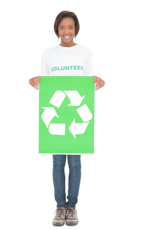 Smiling volunteer woman holding recycling sign on white background photo