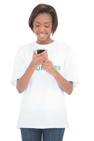 Cheerful volunteer woman looking at her mobile phone on white background photo