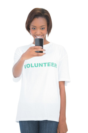 Happy volunteer woman using her mobile phone on white background photo