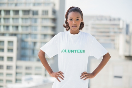 unsmiling: Serious woman with hands on hips wearing volunteer tshirt outdoors on urban background Stock Photo