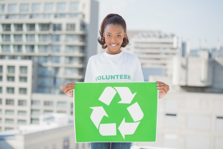 Cheerful woman holding recycling sign outdoors on urban background photo