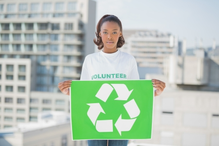Serious volunteer woman holding recycling sign outdoors on urban background  photo