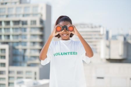 altruism: Mujer sonriente con la camiseta de voluntario con prismáticos al aire libre en medio urbano