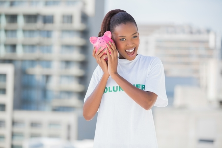Happy cute volunteer holding piggy bank outdoors on urban background photo
