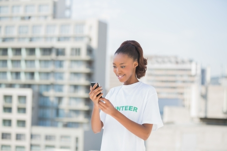 Smiling volunteer holding her mobile phone outdoors on urban background