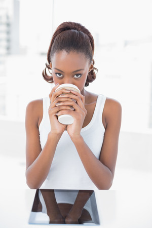 Happy sporty model drinking coffee in bright fitness studio photo