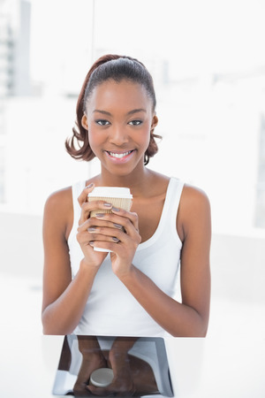 Happy sporty model holding coffee in bright fitness studio photo