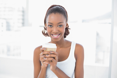 Cheerful sporty model holding coffee in bright fitness studio photo