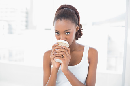 Cute sporty model drinking coffee in bright fitness studio photo