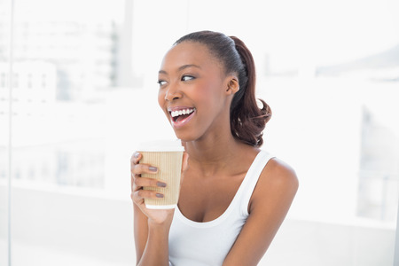 Laughing sporty woman holding coffee in bright fitness studio photo