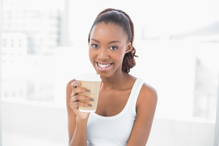 Smiling sporty woman holding coffee in bright fitness studio photo