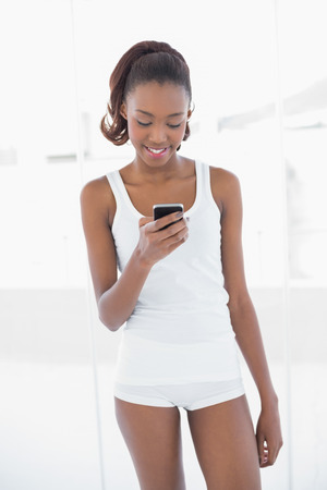 Fit cheerful woman text messaging in bright fitness studio photo