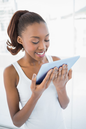 Cheerful sporty woman holding tablet in bright fitness studio Stock Photo - 22323656