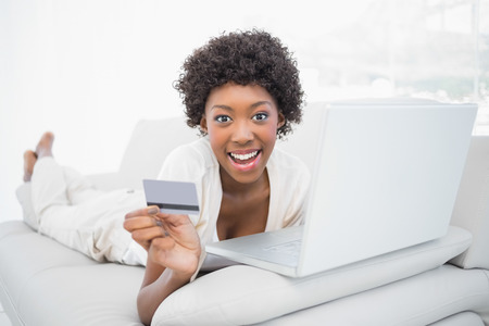 house shopping: Smiling pretty brunette shopping online using her laptop lying on cosy sofa