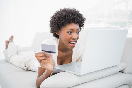 woman shopping: Cheerful pretty brunette shopping online using her laptop lying on cosy sofa