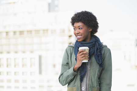 Cheerful casual model holding coffee outdoors on a sunny day photo