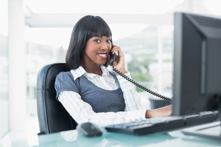 Cheerful businesswoman on the phone while working on computer in bright office photo