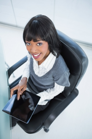 High angle view of smiling pretty businesswoman holding tablet in bright office photo