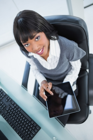 High angle view of cheerful businesswoman holding tablet in bright office photo