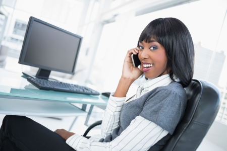 Smiling businesswoman on the phone in bright office photo