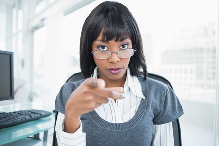 Unsmiling gorgeous businesswoman pointing at camera in bright office photo