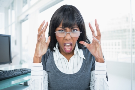 Furious businesswoman screaming in bright office photo