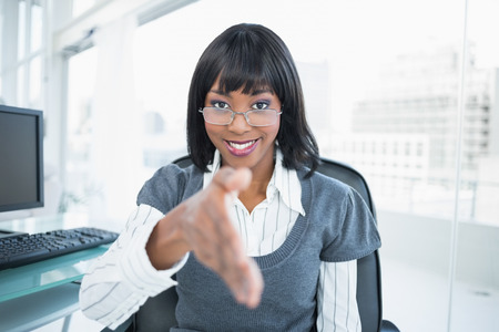 Smiling gorgeous businesswoman offering hand in bright office photo