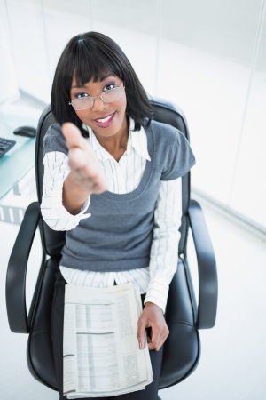 Friendly businesswoman in bright office offering hand  photo
