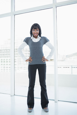 Businesswoman standing in bright office hands on hips photo