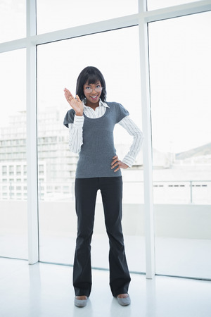Smiling businesswoman waving standing in bright office photo