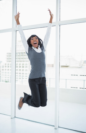 Happy businesswoman jumping in bright office photo