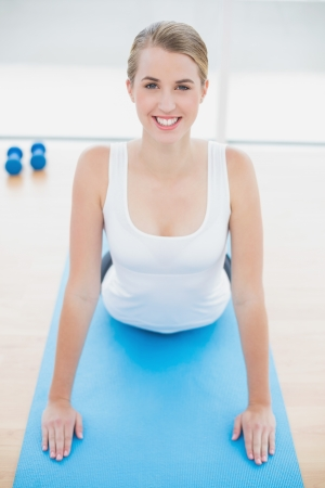 Smiling fit woman stretching on sport mat in bright sports hall photo