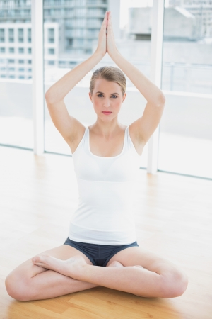 Serious fit woman in lotus position doing yoga session in bright sports hall photo
