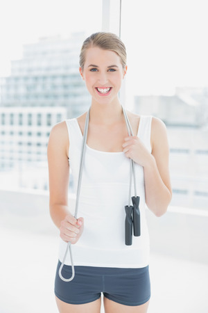 Smiling sporty woman holding skipping rope in bright sports hall photo