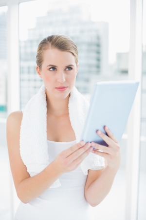 Thoughtful sporty woman in bright sports hall holding tablet pc photo